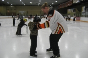 Castlegar Rebels Captain Carson Wornig helps five-year-old Dawson Pytel dazzle the rink with his new skating skills.