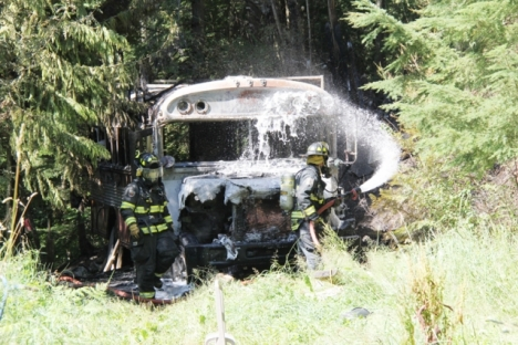 Nelson firefighters spray foam on a Bluebird bus after fire gutted the late 70s model Sunday afternoon. — Bruce Fuhr photo
